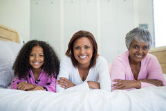 Happy family lying on bed in bed room. Portrait of happy family lying on bed in bed room at home Stock Photos