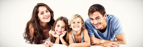 Happy family lying on a bed. Together in the bedroom stock photo