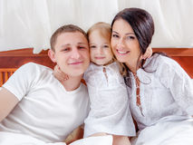 Happy family lying on a bed together Royalty Free Stock Photos