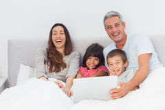 Happy family lying in bed using their laptop Stock Photography
