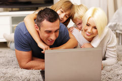 Happy family lying on the carpet at home Royalty Free Stock Photos