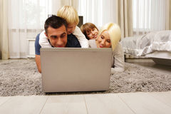 Happy family lying on the carpet and playing Stock Images