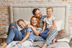 Happy family lying down on bed at home Royalty Free Stock Photo