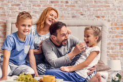 Happy family lying down on bed at home Stock Images
