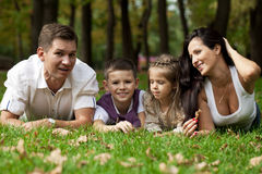 Happy family lying down in the garden Royalty Free Stock Photography