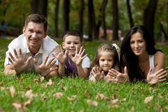 Happy family lying down in the garden stock images