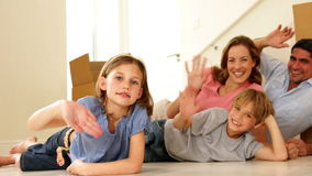Happy family lying on floor in their new home waving at camera stock video footage