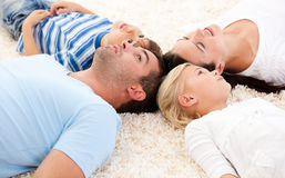 Happy family lying on the floor together Royalty Free Stock Image
