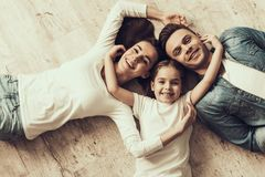 Happy Family Lying of Floor Together at Home. Beautiful Woman Handsome Man and Adorable Little Girl Lying on Parquet Floor and Hugging. Parents and Child stock images