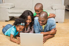 Happy family lying on the floor using laptop Royalty Free Stock Photos