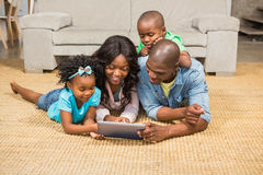 Happy family lying on the floor using tablet Royalty Free Stock Photos