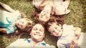 Happy family lying on the grass in a circle Royalty Free Stock Photos