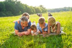 Happy family lying on the grass. Stock Images