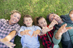 Happy family lying on the grass and making hand gestures Stock Photo