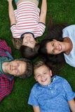 Happy family lying on grass in park Stock Photo