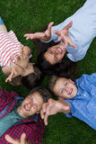 Happy family lying on grass in park Stock Photos