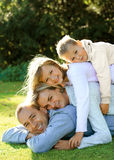 Happy family lying on the grass. And smiling Royalty Free Stock Image