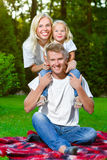 Happy family lying on the grass in summer. Picnic. Concept Stock Photography