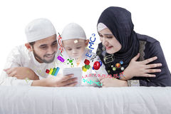Happy family lying and learning on bed Stock Image