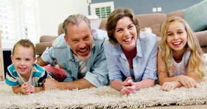 Happy family in lying on rug in living room