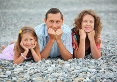 Happy family lying on stony beach, focus on father Stock Photography