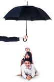 Happy family lying in studio under umbrella. Image of two cheerful parents and their daughter lying in the studio under umbrella. Life and family insurance Royalty Free Stock Photos
