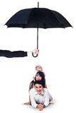 Happy family lying in studio under umbrella. Image of two cheerful parents and their daughter lying in the studio under umbrella. Life and family insurance Stock Image