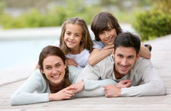 Happy family lying by the swimming pool Stock Image