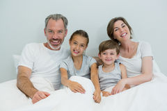 Happy family lying together on bed in bedroom at home Stock Photos