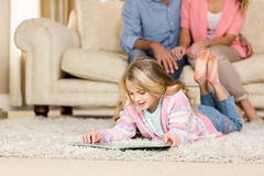 Happy family lying together on the floor Stock Images