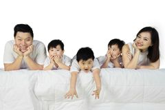 Happy family lying together in the studio. Picture of happy family lying together on the bed, isolated on white background stock photo