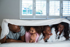 Happy family lying under a blanket on bed Stock Photo