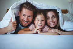 Happy family lying under a blanket on bed Stock Photography