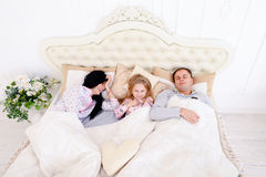 Happy family lying in a white bed and sleep. Mother, father and Royalty Free Stock Photos