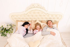 Happy family lying in a white bed and sleep. Mother, father and stock photo