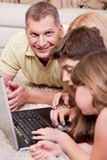 Happy family lying and working with lap top Royalty Free Stock Images