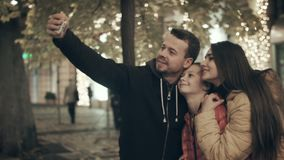 A happy family makes selfi in the lights of the city. Dad, mom and daughter are taking pictures of the selfie phone stock video
