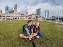 Happy family makes selfie on the background on background of Merdeka square and Sultan Abdul Samad Building. Traveling. Happy family makes selfie on background stock photography