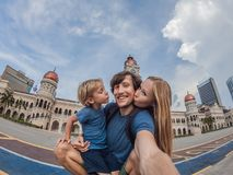 Happy family makes selfie on the background on background of Merdeka square and Sultan Abdul Samad Building. Traveling. Happy family makes selfie on background royalty free stock image