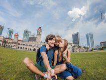 Happy family makes selfie on the background on background of Merdeka square and Sultan Abdul Samad Building. Traveling. Happy family makes selfie on background royalty free stock images