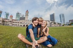 Happy family makes selfie on the background on background of Merdeka square and Sultan Abdul Samad Building. Traveling with childr. Happy family makes selfie on stock image