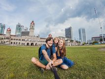 happy family makes selfie on the background on background of Merdeka square and Sultan Abdul Samad Building. Traveling with child stock images