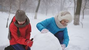 Mom and two daughter sculpt snowman. A happy family makes a snowman outside in winter. stock video footage