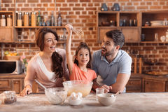 Happy family making cake together in kitchen. `portrait of happy family making cake together in kitchen Stock Image