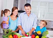 Happy family making dinner together in the kitchen Royalty Free Stock Images