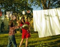 Happy family making laundry outside, children Royalty Free Stock Image