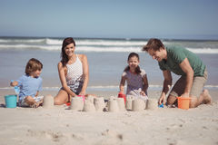 Happy family making sand castle at beach Stock Images