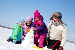 Happy family making snowman Stock Photo