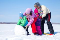 Happy family making snowman Royalty Free Stock Images