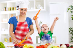 Happy family making vegetables vegetarian meal. At home Stock Photos